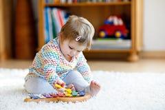 Förtjusande gulliga härliga små behandla som ett barn flickan som hemma spelar med bildande trämusikleksaker eller barnkammaren L royaltyfri bild