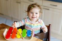 Förtjusande gulliga härliga små behandla som ett barn flickan som hemma spelar med bildande trämusikleksaker eller barnkammaren arkivfoto