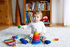 Förtjusande gulliga härliga små behandla som ett barn flickan som spelar med den bildande färgrika trärainboy leksakpyramiden Royaltyfria Foton