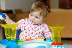 Förtjusande gulliga härliga små behandla som ett barn flickan som spelar med hemmastadda bildande leksaker eller barnkammaren Royaltyfria Foton