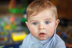 Förtjusande gulliga härliga små behandla som ett barn pojken som spelar med bildande färgrika leksaker på barnkammaren Stående av Royaltyfri Bild