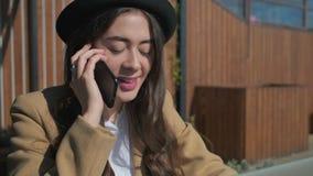 Förtjusande kvinna som har konversation över telefonen arkivfilmer
