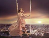 Förtjusande kvinna som svänger ovanför staden royaltyfria bilder