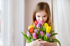 Förtjusande le liten flicka med tulpan Fotografering för Bildbyråer