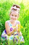 Förtjusande le liten flicka på ängen med blommor Arkivfoto