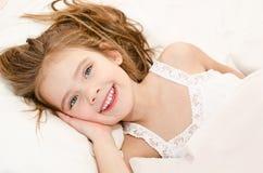 Förtjusande le liten flicka som vaknas upp arkivfoton