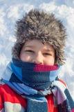 Förtjusande le pojke på snöbakgrunden royaltyfri bild