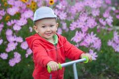 Förtjusande le pojke som spelar i trädgården Arkivbilder