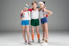 Förtjusande le sportiga ungar i sportswearen som tillsammans står på grå färger royaltyfri bild
