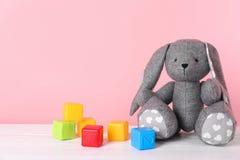 Förtjusande leksakkanin och plast- kuber på tabellen mot färgbakgrund, utrymme för text fotografering för bildbyråer