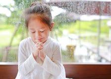 Förtjusande liten asiatisk flicka som ber på exponeringsglasfönster på den regna dagen Andlighet och religion arkivfoto