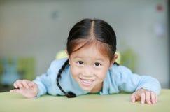 Förtjusande liten asiatisk flicka som lägger på barntabellen med att le och att se kameran, lyckliga ungar arkivbilder