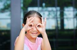 Förtjusande liten asiatisk flicka som ser till och med imaginärt binokulärt arkivbild