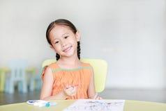 Förtjusande liten asiatisk flickateckning och målning med vattenfärg på papper i barnrum royaltyfria foton