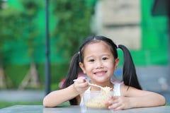 Förtjusande liten asiatisk ungeflicka som äter ögonblickliga nudlar i morgonen på trädgården royaltyfri bild