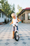 Förtjusande liten blond pojke med cykeln Arkivbilder