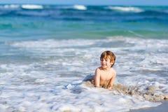 Förtjusande liten blond ungepojke som har gyckel på havstranden Upphetsat barn som spelar med vågor, simning, plaskande och lyckl royaltyfri bild