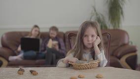 Förtjusande liten flicka för stående som äter kakor som sitter på tabellen och ser kameran Suddigt diagram av ungt arkivfilmer