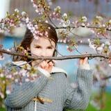 Förtjusande liten flicka i blommande körsbärträdgård Arkivfoto