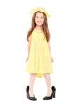 Förtjusande liten flicka i infallgulingklänning och hatt Royaltyfri Foto