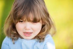 Förtjusande liten flicka med det ledsna uttryckt av hennes framsida som går att gråta royaltyfri fotografi