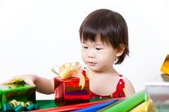 Förtjusande liten flicka med gåva, i chirstmasdag Arkivfoton