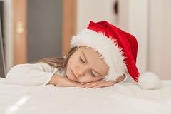 Förtjusande liten flicka med julhattliten flicka som sover, a arkivfoton