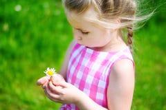 Förtjusande liten flicka med tusenskönan på solig sommardag Royaltyfria Foton