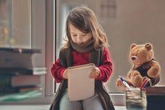 Förtjusande liten flicka och att skriva brevet till jultomten som sitter på en vind Fotografering för Bildbyråer