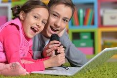 Förtjusande liten flicka och pojke som sjunger karaoke royaltyfria bilder