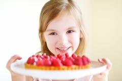 Förtjusande liten flicka och raspbrerry kaka Arkivbilder