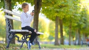 Förtjusande liten flicka på den härliga höstdagen utomhus Gullig unge på bänken i nedgång lager videofilmer