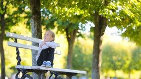 Förtjusande liten flicka på den härliga höstdagen utomhus Gulligt ungesammanträde på bänken i utomhus- parkerar i nedgång lager videofilmer