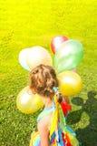 Förtjusande liten flicka på grönt gräs med färgrika ljusa ballonger arkivbilder