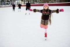 Förtjusande liten flicka på isisbanan Arkivfoto