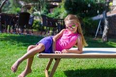 Förtjusande liten flicka på stranddagdrivare utomhus royaltyfria bilder