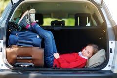 Förtjusande liten flicka som är klar att gå på semestrar med hennes föräldrar Lura att koppla av i en bil för en vägtur royaltyfri fotografi
