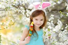 Förtjusande liten flicka som äter färgrika gummigodisar på påsk Royaltyfri Foto