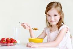 Förtjusande liten flicka som äter sädesslag i ett kök Arkivbild