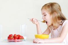 Förtjusande liten flicka som äter sädesslag i ett kök Royaltyfri Foto