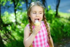 Förtjusande liten flicka som äter smaklig glass på sommardag Arkivfoto
