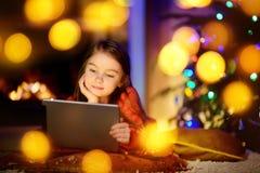 Förtjusande liten flicka som använder en minnestavlaPC vid en spis på julafton royaltyfri bild