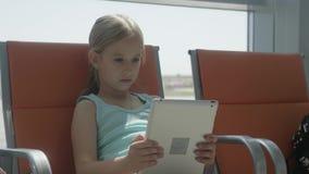 Förtjusande liten flicka som använder minnestavlan på flygplatsen, medan vänta på deras flyg Resande utland med ungar stock video