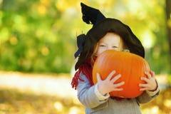 Förtjusande liten flicka som bär den halloween dräkten som har gyckel på en pumpalapp på höstdag arkivbild