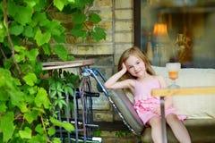 Förtjusande liten flicka som dricker orange fruktsaft Royaltyfri Bild