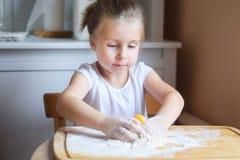Förtjusande liten flicka som gör degen för pasta Arkivbild