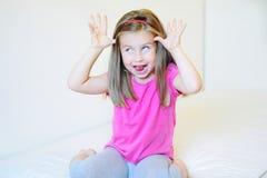 Förtjusande liten flicka som gör roliga framsidor Arkivbild