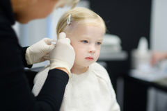 Förtjusande liten flicka som har örapiercingprocess i skönhetmitt Arkivfoton