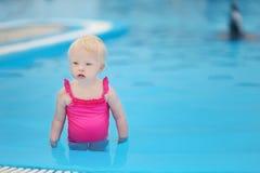 Förtjusande liten flicka som har gyckel i en simbassäng Arkivbild