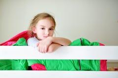 Förtjusande liten flicka som har gyckel i tvilling- britssäng Royaltyfri Fotografi